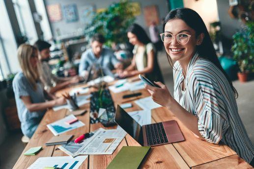 Job Berufsanwärter Steuerberater - Frau mit Brille Sitz am Tisch und lächelt in die Kamera