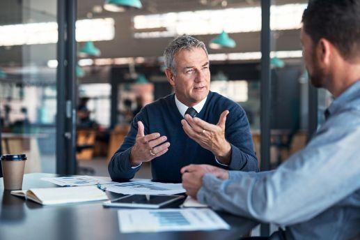 Job Bilanzbuchhalter Bludenz - Mann im gespräch mit anderer Person sitzend an Tisch