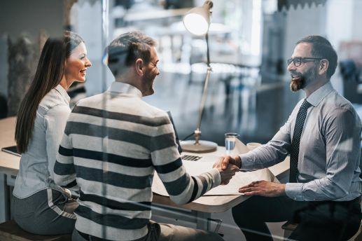 Job Personalverrechner Bludenz - Mann im Gespräch mit Paar schüttelt anderer Person die Hand
